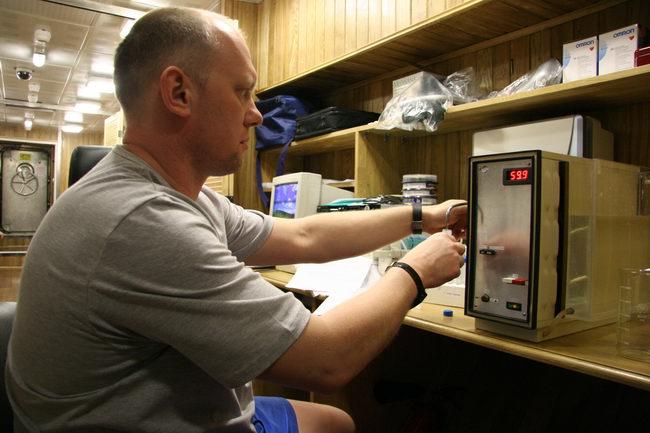 Первый месяц 105-суточной изоляции. Олег Артемьев выполняет метод по оценке эффективности процесса обеззараживания и нагрева питьевой воды в СЖО СВЧ-энергией.