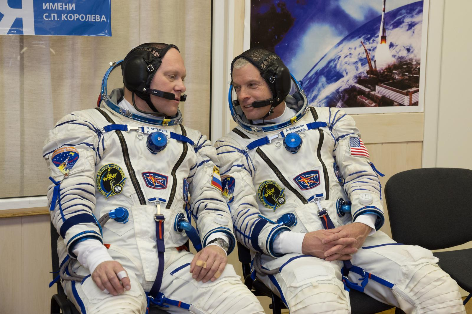 """2014-03-14-12-43-15[1]In the Integration Facility at the Baikonur Cosmodrome in Kazakhstan, Expedition 39/40 Flight Engineer Steve Swanson of NASA (right) shares a word with crewmate and Flight Engineer Oleg Artemyev of the Russian Federal Space Agency (Roscosmos) during a """"fit check"""" dress rehearsal March 14 that is part of the crew's final training. Swanson, Artemyev and Soyuz Commander Alexander Skvortsov of Roscosmos are scheduled to launch to the International Space Station March 26 (Kazakh time) for the start of a six-month mission.NASA/Victor Zelentsov"""